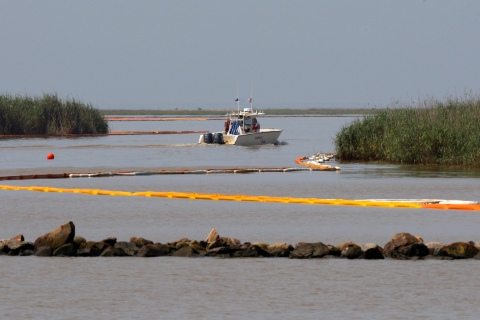 A boat floats past containment booms anchored around the Mississippi River