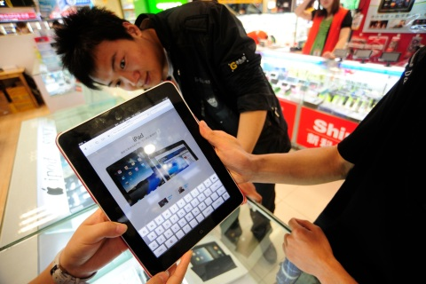 A shop assistant displays an iPad at an electronic products store in Hefei