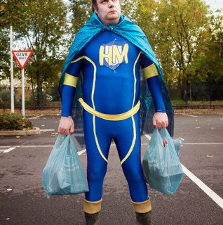 Overweight Man Dressed as Hero Holding Shopping Bags