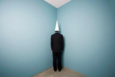 Businessman Wearing Dunce Cap Standing in Corner