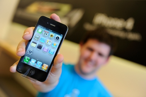 Ben Paton from Somerset, the first person to buy the new Apple iPhone 4 in Britain, poses with his phone inside the Apple store in central London