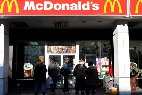 People stand outside a McDonald's restaurant in Harlem in New York
