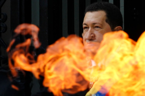 Venezuelan President Hugo Chavez greets supporters as he stands behind a flame from the torch at the entrance of Simon Bolivar's tomb in Caracas