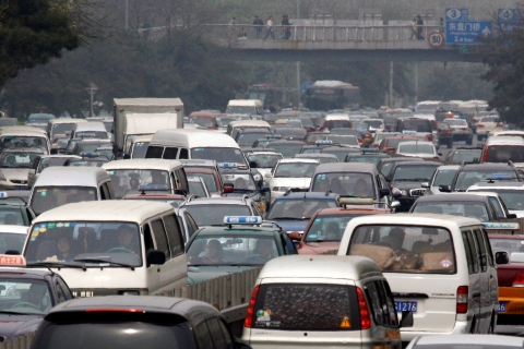 Cars sit in a traffic jam as they make their way along a main road in central Beijing