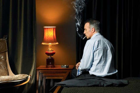 Man sitting on bed smoking a cigarette