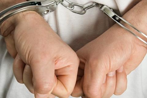 A criminal wearing handcuffs