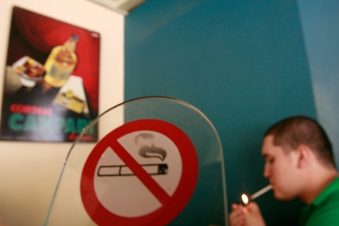 A man lights a cigarette in a cafe in Athens