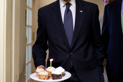 President Barack Obama watches the flame on the candle as he walks to the Brady Briefing Room to present cupcakes to Hearst White House columnist Helen Thomas in honor of her birthday in this official handout photo