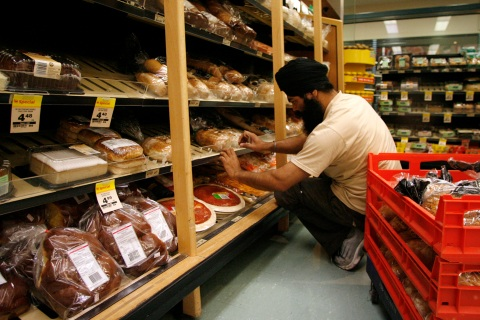 A worker arranges loaves of bread at a Woolworths supermarket in Sydney