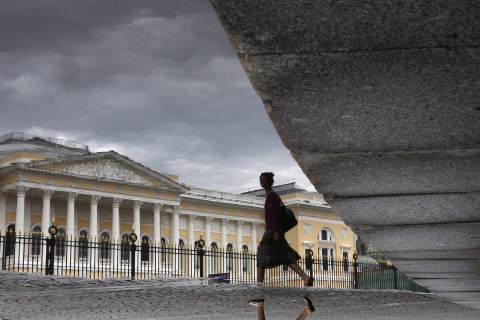 A woman walks in front of the Russian Museum in St. Petersburg