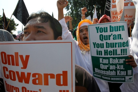 Members of the Islamic group Hizbut Tahrir Indonesia hold placards during a protest in front of U.S. embassy in Jakarta