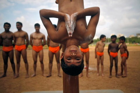 A boy performs Mallakhamb (gymnast's pole) during a practice session at a playground in Mumbai
