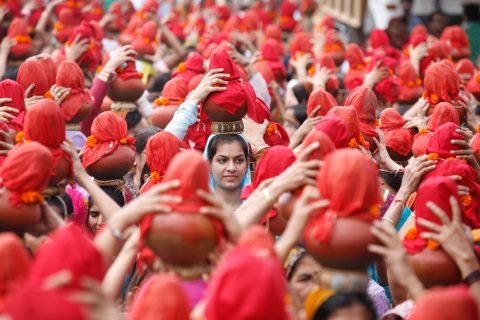 People carry earthen water pots as they take part in a Jhulelal Chaliha procession in Ahmedabad