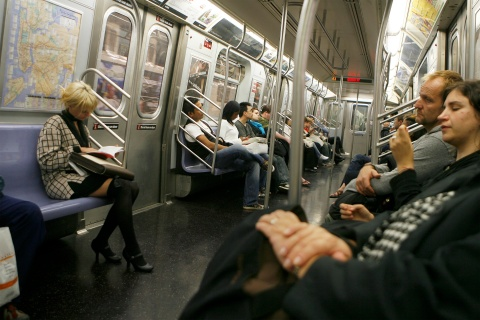 Commuters ride a subway car in New York