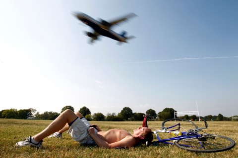 A plane passes over a man working on his suntan in Washington