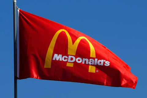 A flag blows in the wind above a McDonald's restaurant