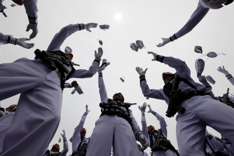Indonesia's Navy servicemen throw their hats into the air to celebrate the 65th anniversary of the Indonesia National Military in Jakarta