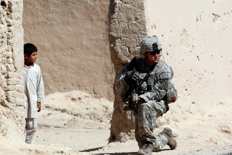 A boy looks at a U.S. soldier from Alpha Company, 1-22 Infantry Battalion, taking up position while on patrol in Kandahar province in southern Afghanistan