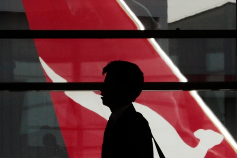 Passenger walks in front of the tail of a Qantas plane at Sydney airport