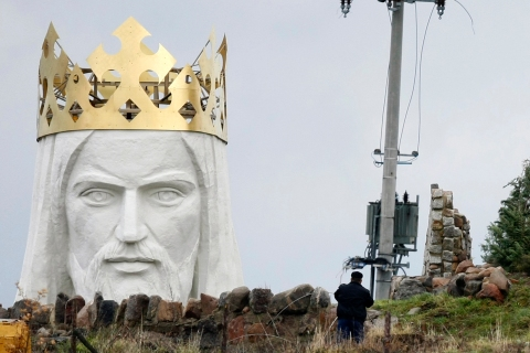 A man stands near the crowned head of a statue of Jesus being built in Swiebodzin