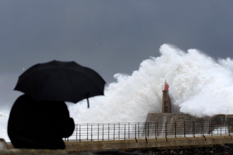 A man looks at waves crashing against a lighthouse in the northern Spanish village of Viavelez