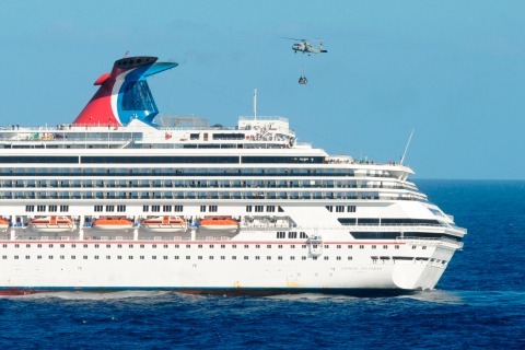 Handout shows a U.S. Navy HH-60H Sea Hawk helicopter delivering supplies to the Carnival cruise ship C/V Splendor sitting adrift off the Mexican coast