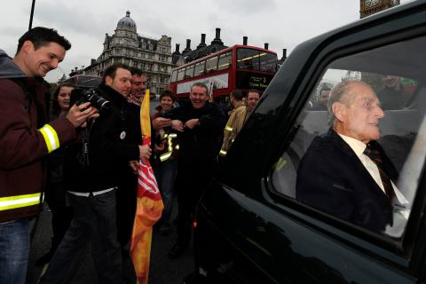 Britain's Prince Philip sits in his chauffered car as it is caught in traffic caused by protesting fire fighters walking towards Downing Street in London