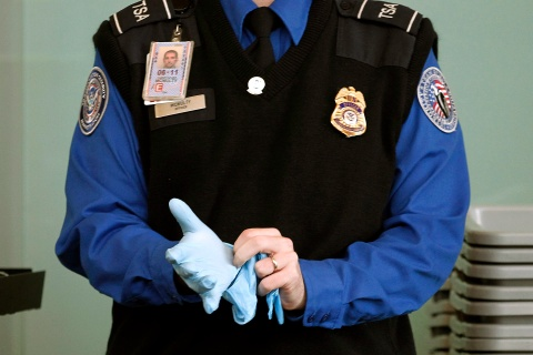 A TSA agent dons rubber gloves at Washington Reagan National Airport.