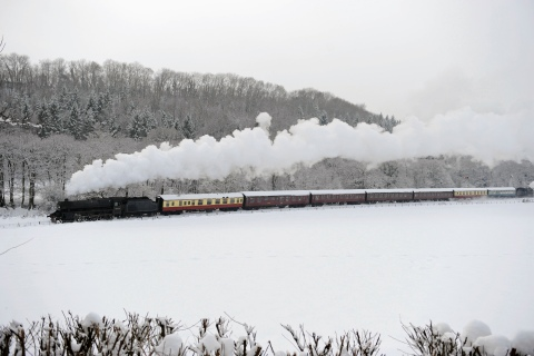 A steam train running through a snow covered valley in northern England