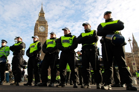 Police officers stand in Parliament Square, before a student protest, in central London