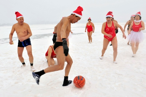 Winter swimmers wearing Santa Claus hats, play with a ball on a snow-covered river in Shenyang