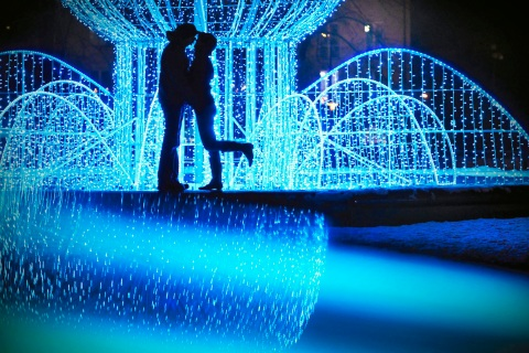 A couple stand at illuminated Plac Baczynskiego in Tychy