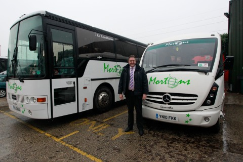 Adrian Morton, the owner of Mortons Travel, poses by two of his coaches