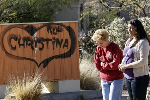 Woman stand near sign before funeral for Christina Green in Tucson