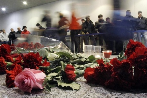 People walk past flowers left on a floor in memory of those killed in Monday's blast at Moscow's Domodedovo airport
