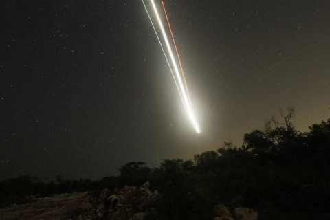The lights of an approaching plane are pictured as a meteor streaks past stars in the night sky, on the outskirts of Cancun