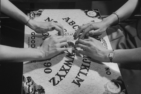 People playing with a Ouija Board.
