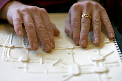 Blind man reading braile map of London Underground tube with fingers
