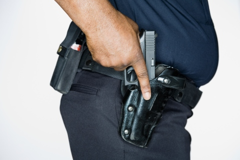 78567845 African American male police officer with hand on gun