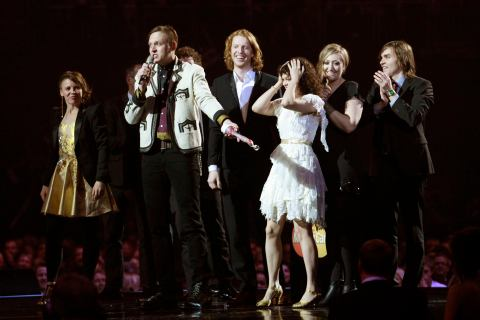 Members of Arcade Fire react after winning the International album at the BRIT awards in London