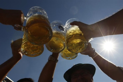 People toast with beer mugs at Munich's Oktoberfest