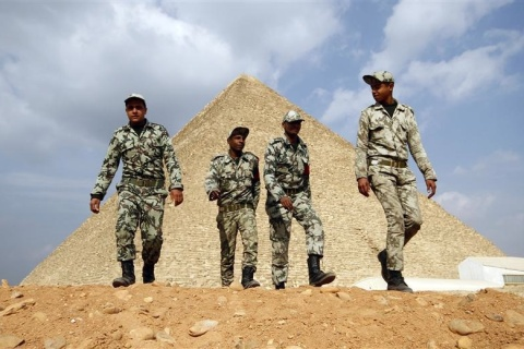 Egyptian soldiers walk in front of the Great Giza pyramids on the outskirts of Cairo