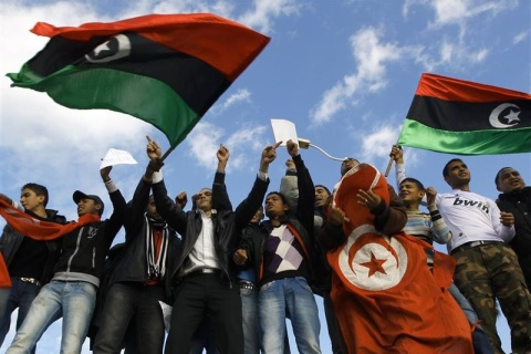 Tunisians hold Tunisian and Kingdom of Libya flags during an anti-Gaddafi protest at the Tunisian Libyan border crossing of Ras Jdir