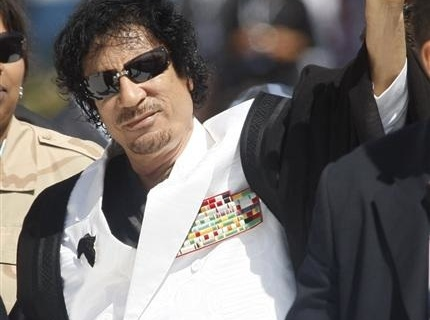 Libya's leader Muammar Gaddafi gestures as he arrives for a final round table session at the G8 summit in L'Aquila
