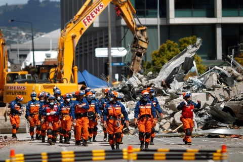 Japanese rescue workers walk past the rubble of the CTV building in Christchurch