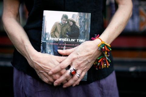 Suze Rotolo, an author, poses with her book in the Greenwich Village section of New York