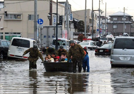 Soldiers pull a boat across floodwater a