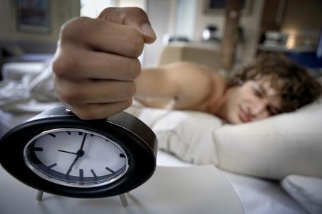 89697489 Man hitting alarm clock