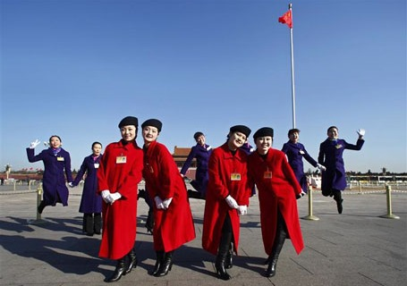 Hostesses pose for a photo on Tiananmen Square during a plenary session of the National People's Congress in Beijing