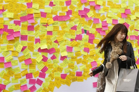 A woman walks away from a message wall after writing a message to the victims of last week's earthquake and tsunami in Japan in central Seoul